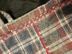 Herringbone embroidery stitches in pearl cotton on the neckline and side seam of the wool plaid Viking Age apron dress.