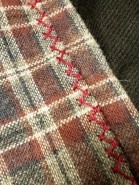 Herringbone embroidery stitches in pearl cotton on the neckline of the wool plaid Viking Age apron dress.