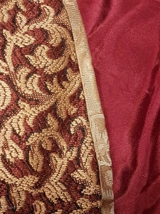 Gold silk bias on hem of red and gold Italian over dress the red striped lining is also visible.