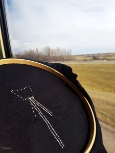 Starting the embroidery on the black apron panel (showing the wrong side of the work) on the drive up to Edmonton