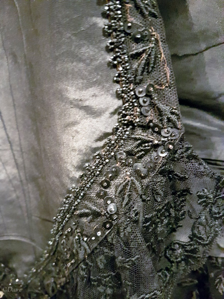 Close up of Queen Victoria's dress details showing the lace, beading and sequins.