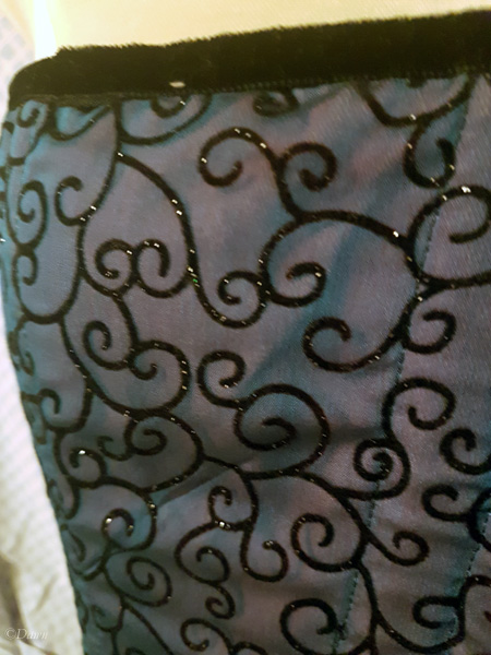 Close up on the upper edge of the blue flocked scroll overbust  corset (photographed without flash)
