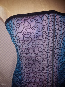 Blue flocked overbust corset. Close up taken with flash so you can see the pink fabric underneath.