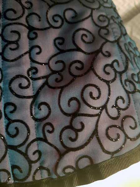 Close up on the lower edge of the blue flocked scroll overbust  corset (photographed without flash)