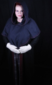 Photo credit ©Mysticus Photography - Me in my steel grey wool hood, along with other elements of my Viking Age Norse costume. These include my red and black coat, my plaid apron dress (hangerock), my green wool dress (serk) and my hand-spun naalbound wool mittens.