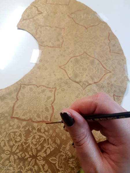 Painting gold damask with fabric paint to highlight the elements.