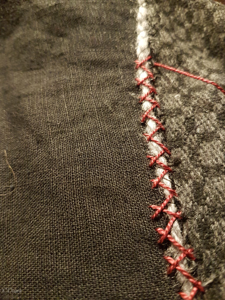 Hand-stitched herringbone stitch in red pearl cotton to sew the facing to the rest of the Viking Age apron dress / hangerock. the stitches go over a wool yarn which acts as a seam allowance treatment to reduce fraying.