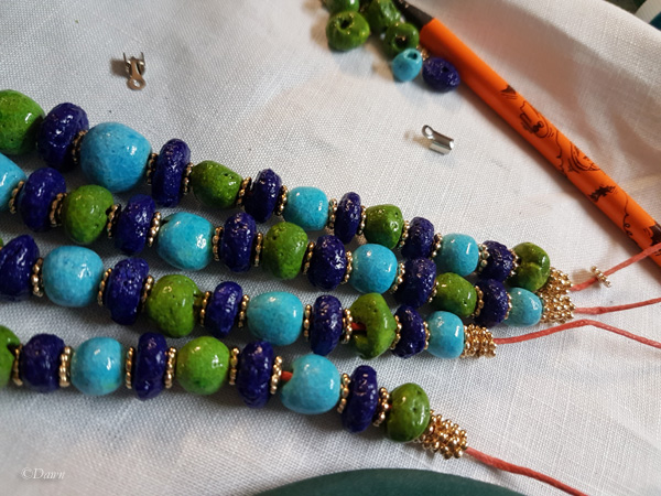 Stringing Egyptian faience beads for a necklace