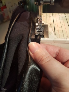 Sewing folded wet-look spandex raw edges together on the edge of my tank top. This will bind the edge.