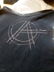 Anarchy symbol marked in chalk on my tank top.
