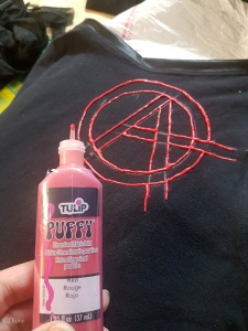 "Using Tulip Puffy paint to draw the outline of the Anarchy symbol on my ""smells like teen spirit"" cheerleader tank top."