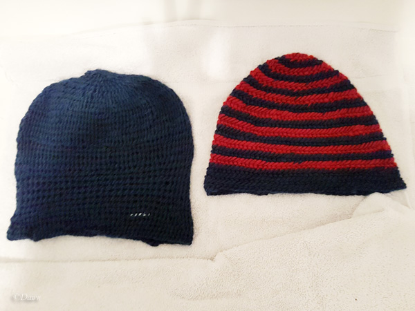Blocking two naalbound hats. The blue one is York stitch, while the striped one is Oslo stitch.
