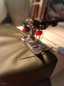 Using a twin-needle stitch for the hem of the green PVC circle skater skirt.