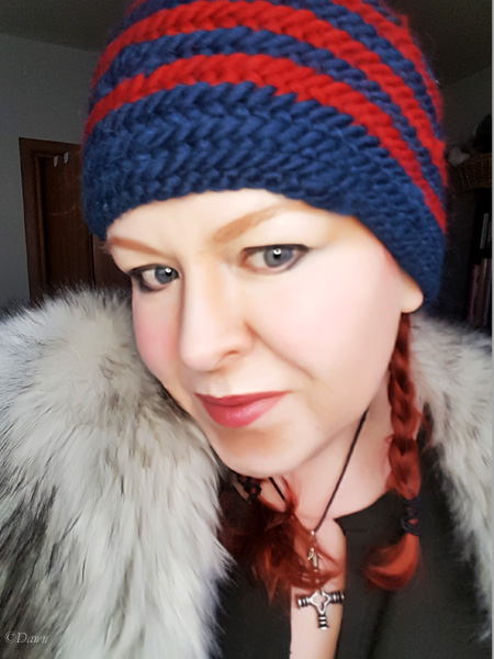Selfie wearing my new spiral-striped red and blue naalbound hat. The hat was made using the Oslo stitch.