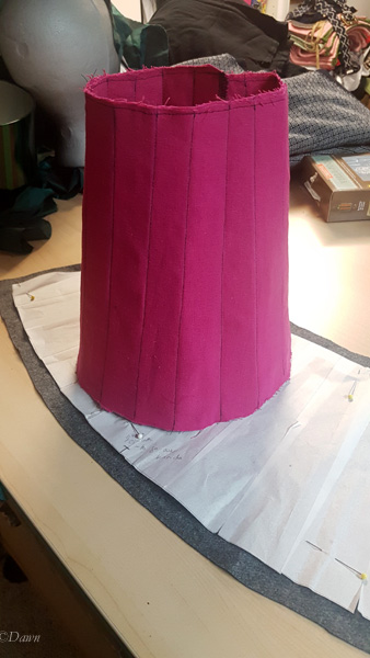 The base of the packable truncated hennin (pink linen) fully boned with the supports, on top of the 'fashion fabric' about to be cut out.
