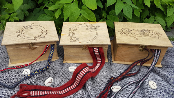 Three of the pyrography embellished wooden boxes I made, displayed with tablet weaving.