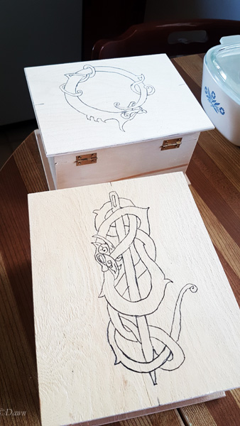 Boxes from the dollar store with Viking - inspired designs transferred onto the lids with carbon paper.