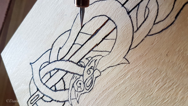 Tracing over the design of a dragon/serpent with a wood-burning kit.