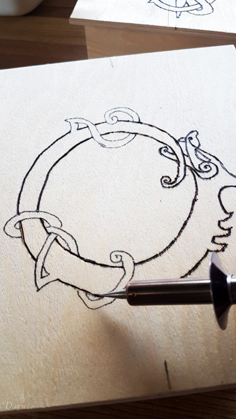 Tracing over the design of a dragon / serpent / ouroboros with a wood-burning kit.