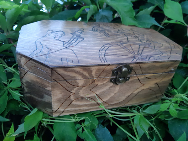 Wood burned box with a medieval woodcut image of three women in the process of producing yarn on the lid.