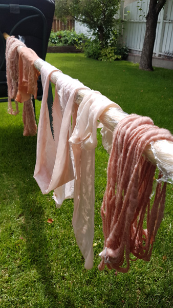 Handspun wool yarn and linen and silk fabrics drying in my backyard after being dyed with avocado pits and skins