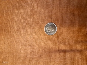 Brown herringbone twill fabric for sale. Quarter for scale.
