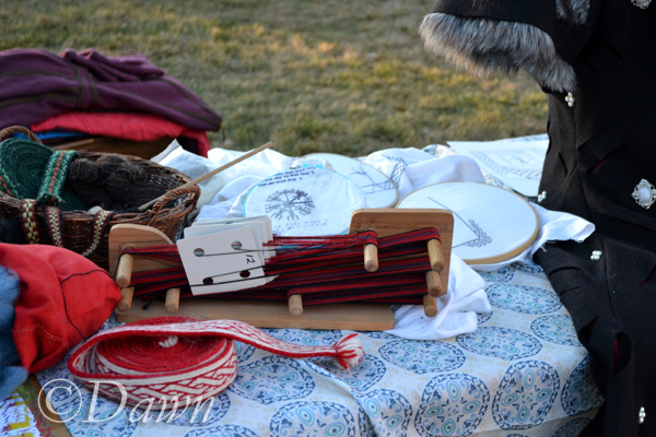 Table of fibre arts from carding wool, to spinning it, weaving it, and finally the finished tablet woven trim/belt at the Ghoul's Night Out at Heritage Park