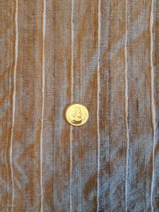 Tan and white striped silk fabric. Quarter for scale of stripe