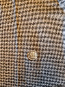 Tan & black houndstooth wool/silk blend fabric. Quarter for scale of weave