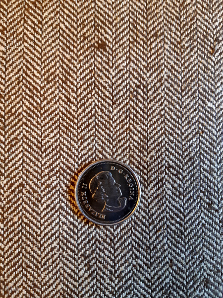 Brown and tan herringbone fabric for sale. Quarter for scale of weave