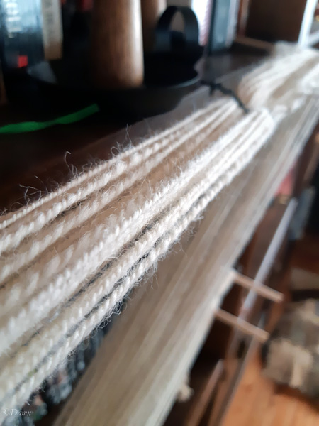 Two-ply handspun Romney natural white wool yarn on my makeshift warping board preparing for setting the twist.