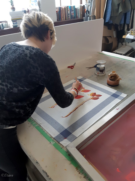 A fellow student touching up minor errors in her printing with a paintbrush