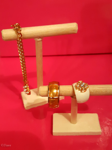 short and tall wooden necklace and bracelet display stands for doll dioramas.