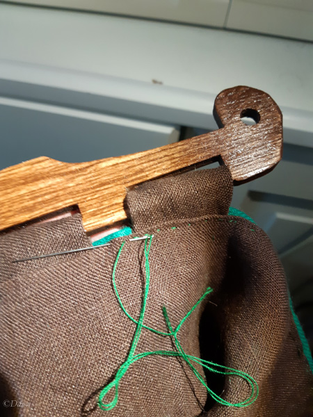 Hand-sewing the linen lining in place over the handle tabs. The tabs attach the wooden handle to the fabric bag.