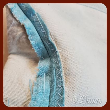 Using large hand stitches to hold the seam allowance down on the side seams of the interlining + lining